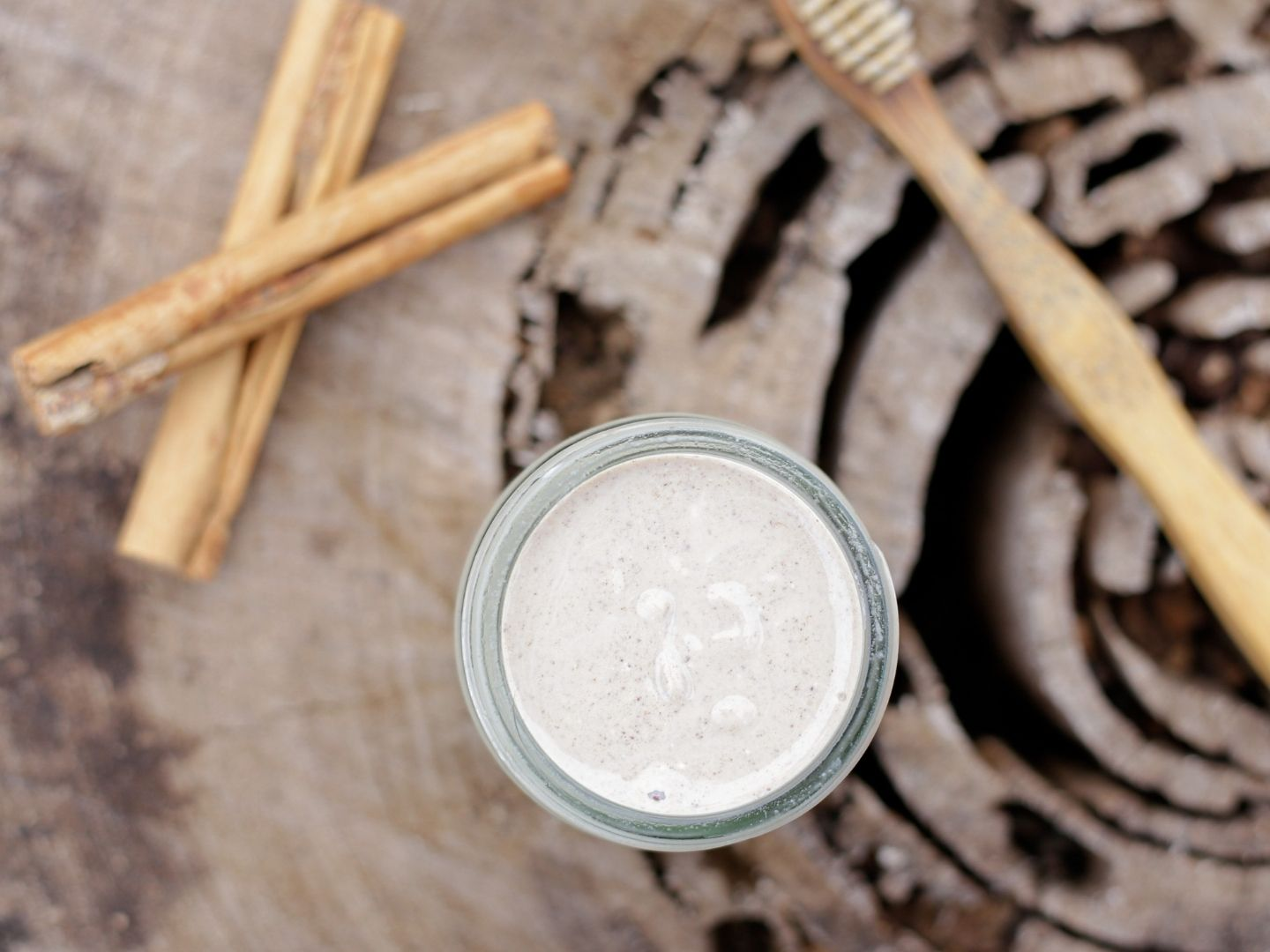 Homemade cinnamon toothpaste with cinnamon sticks and toothbrush in background